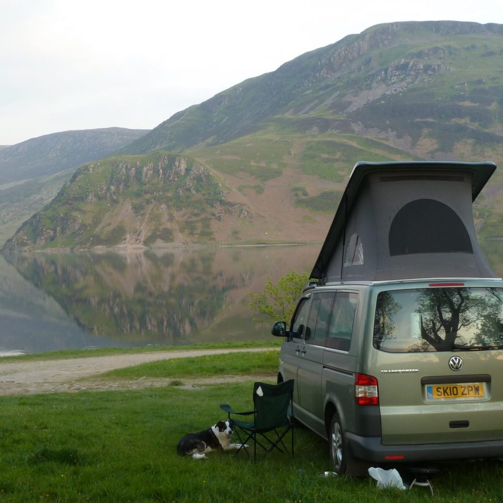 campervan next to a loch with a dog