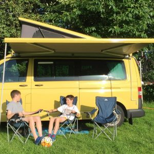 yellow campervan with kids sitting in front