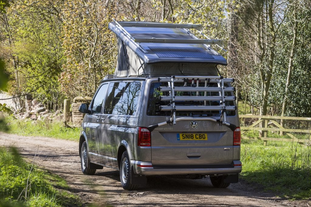 Campervan with a Pop Top Roof on the road with trees and grass on the background