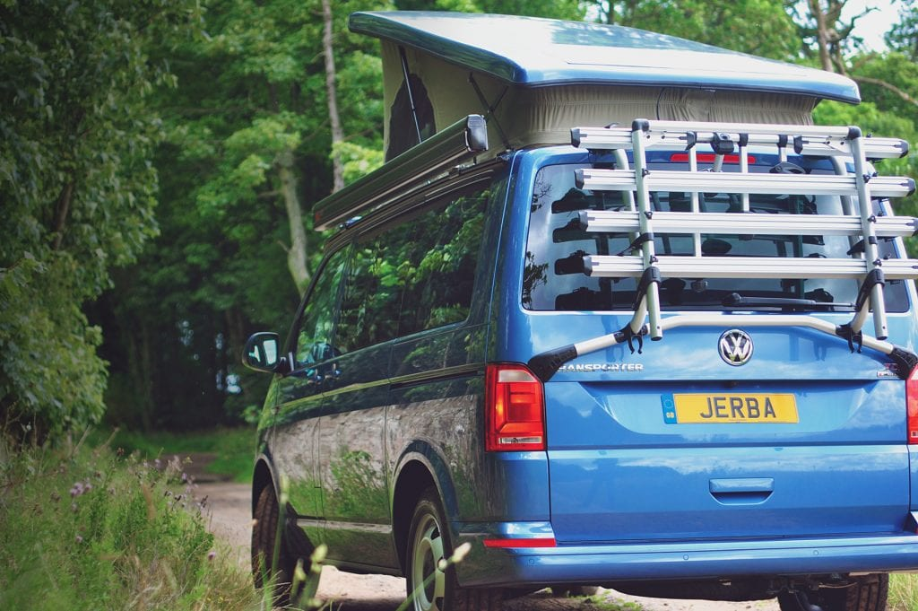 Blue Campervan with a Pop Top Roof near the forest