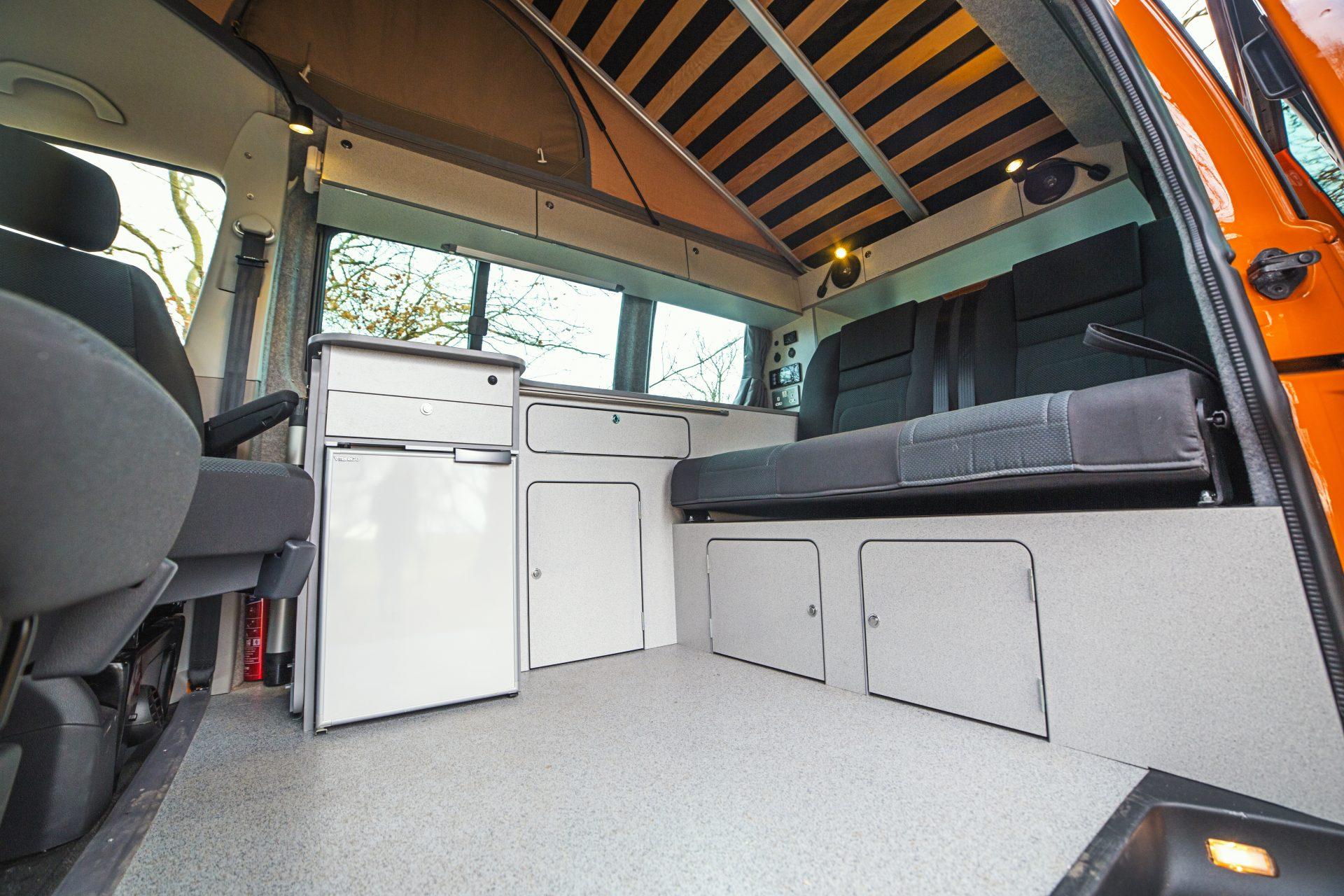 Campervan Interior - light coloured cupboards and black seats